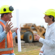 Two construction workers arguing on either side of a pole